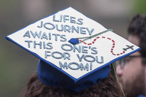 """graduate with sign reading """"Life's journey awaits; this one's for you, mom!"""""""
